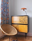Bamboo armchair in front of wall cabinet with lamp