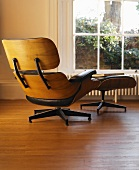 Armchair and footstool with leather upholstery in front of window