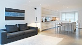 Open-plan living room with sofa, dining area and kitchen