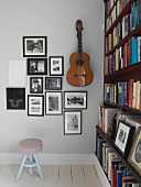 Black and white photographs and guitar on wall next to bookcase