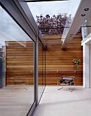 Designer house- Bauhaus armchair in modern courtyard with lighting integrated into glass roof