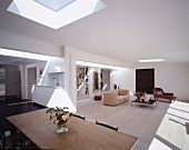 Large, open-plan living space with sunny skylights above seating area, dining table and kitchen unit