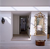 View into raised hall with open apartment door between exotic mask and mirror framed with gold leaves