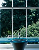 Designer washstand with blue glass slab in front of lattice window with view of trees