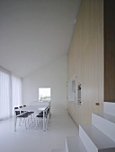 Steps to modern meeting room with kitchenette integrated into wall cupboards