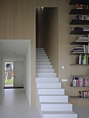 Staircase with solid, white steps next to view of hall with window element in front door