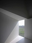 Sunlight falling through frameless glazed wall aperture in modern, empty room