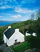 Altes, irisches Bauernhaus mit Kaminen in den Giebelfassaden auf grünem Hügel mit Weitblick