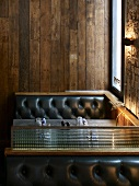 Vintage-look booths - benches with black leather upholstery and brass-coloured retro lamp in front of old wooden wall