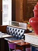 Mixture of colours and styles in English coffee bar - retro-style booths and trendy purple chairs at table for two next to ceramic urn on marble slab