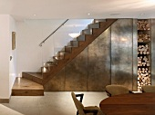 Wood block, designer staircase with glass balustrade and metal elements next to open firewood stack