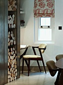 Integrated firewood stack next to office niche with designer chair and Roman blind with floral pattern