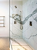 Dramatic marble cladding in floor-level shower with trench drain and glass screen