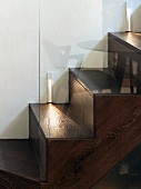 Wood-clad, concrete stairs with lighting and reflections in glass balustrade