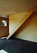 Simple wooden staircase without balustrade and sunlight falling on concrete floor in wooden house with plywood cladding