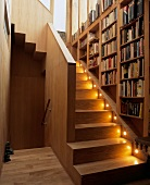 Bookcase above illuminated stairs in stairwell of wooden house
