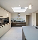 Spacious kitchen with dark wooden fronts on base units and tall cream-coloured cupboards with integrated appliances