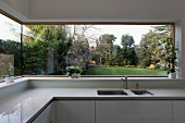 Panoramic window with view of garden in light designer kitchen with Corian work surfaces