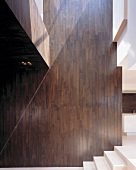 Double-height, wood-clad wall next to steps