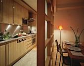 Küche und Esszimmer, abgetrennt durch eine Holz- und Glaswand