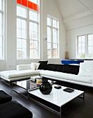 Wohnzimmer mit Sofa, Couchtisch & raumhohen Fenstern