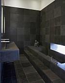 Bathroom tiled in dark grey with bathtub & sink