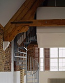 Steel spiral staircase in room with exposed brick walls & roof beams