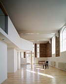 View of room with gallery, brick wall & arched windows