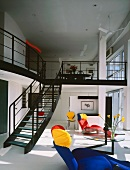 Living room with colourful seating & stairs to gallery