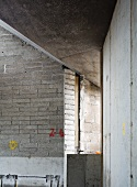 Building under construction - corner of wall in brick and exposed concrete