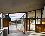 Zeitgenössisches Haus mit offener Terrassendrehtür und Blick auf die Landschaft