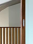 Blick durch offene Schiebetür auf Geländer aus Holz
