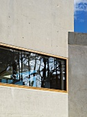 House facade of exposed concrete with horizontal window