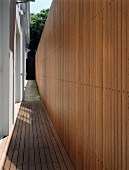 Mini-terrace and exit between house and high wooden wall