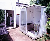 Part glass container with bathroom appliances situated in garden
