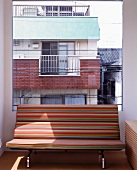 Striped bench in front of large window