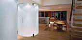 Zylinderförmiger Glaseinbau beleuchtet im offenen Wohnraum