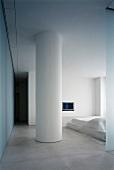 Round, white column in minimalist bedroom
