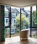 Upholstered armchair in front of glass facade of house