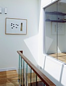 Contemporary stairwell with ceiling-height windows and view of room
