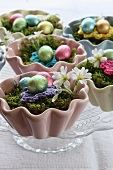 Chocolate eggs on moss in ceramic cupcake cases