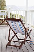 Liegestuhl aus Holz mit gestreiftem Bezug auf einer Dachterrasse