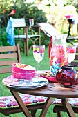 Garden table with colourful crockery, antipasti and storm lamp