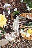 Basket of roses and various garden tools next to flower bed