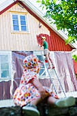 Young woman painting facade of house, little daughter watching