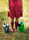 Woman in red Wellington boots standing between two watering cans