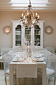 White, Neo-Rococo chairs around set dining table in country-style dining room