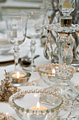 Tealights in glass dishes and candlestick decorated with glass ornaments