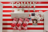 Christmas stockings hanging from traditional bracket shelf on red and white striped wall