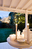 Festive atmosphere on veranda with lit lanterns next to candlesticks on table and view of fairy lights in trees